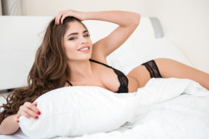 Smiling cute woman in lingerie lying on the bed