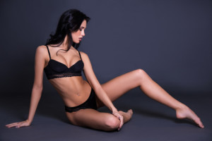 sexy young woman in black lace lingerie sitting over dark gray